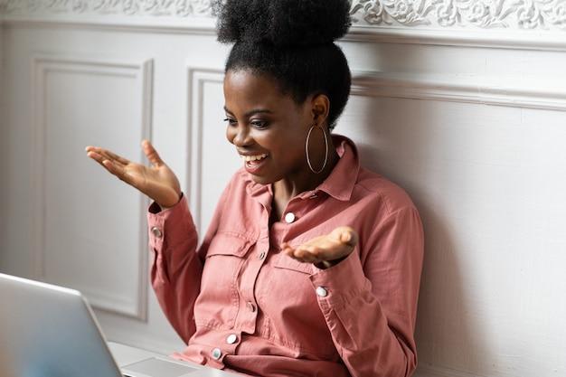 Afroamerikanerfrau mit afro-frisur, die auf laptop arbeitet, mit händen gestikuliert, webcam betrachtet und plaudert