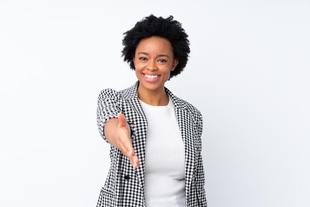 Afroamerikanerfrau mit blazer auf isolierten weißen händeschütteln für das schließen eines guten geschäfts