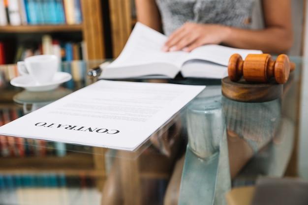 Afroamerikanerfrau mit buch bei tisch mit cup und dokument