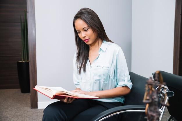 Afroamerikanerfrau mit dem buch, das auf lehnsessel im büro sitzt