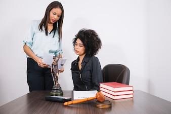 Afroamerikanerfrau mit Dokument nahe Dame bei Tisch mit Taschenrechner, Büchern, Papier und Statue