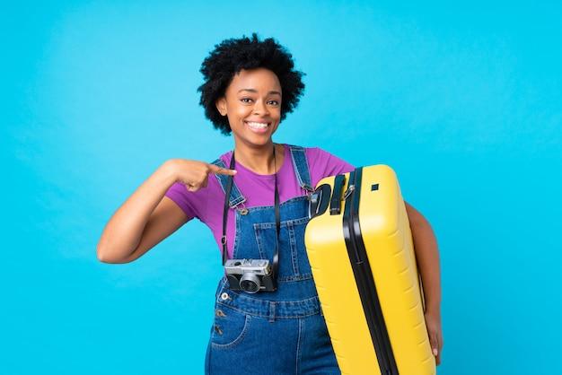 Afroamerikanerfrau mit gelbem koffer über lokalisierter blauer wand