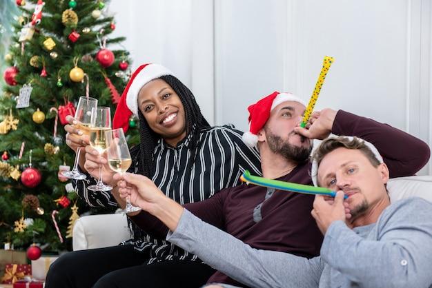 Afroamerikanerfrau mit gruppe freunden, die zu hause weihnachten feiern