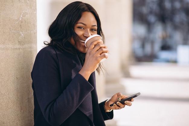 Afroamerikanerfrau mit trinkendem kaffee des telefons