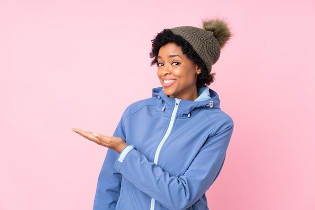 Afroamerikanerfrau mit winterhut über lokalisierter rosa wand