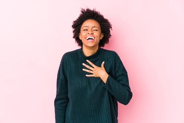 Afroamerikanerfrau mittleren alters auf einer rosa isolierten lacht laut und hält hand auf brust.