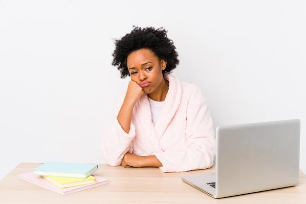 Afroamerikanerfrau mittleren alters, die zu hause arbeitet, die sich traurig und nachdenklich fühlt und leerzeichen betrachtet.