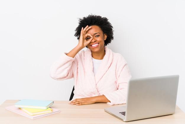 Afroamerikanerfrau mittleren alters, die zu hause arbeitet, isoliert aufgeregt, ok geste auf auge haltend.