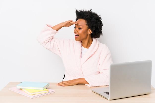 Afroamerikanerfrau mittleren alters, die zu hause arbeitet, isoliert entfernt schaut hand auf stirn hält.