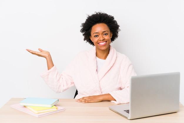 Afroamerikanerfrau mittleren alters, die zu hause arbeitet, lokalisiert, einen kopienraum auf einer handfläche zeigend und eine andere hand auf taille haltend.