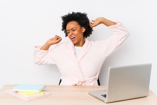Afroamerikanerfrau mittleren alters, die zu hause arbeitet und arme streckt, entspannte position.