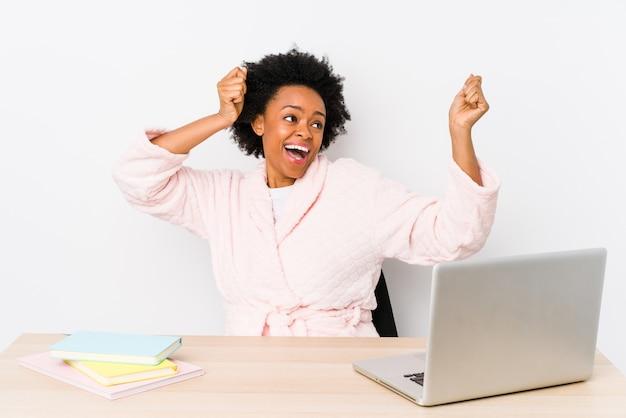 Afroamerikanerfrau mittleren alters, die zu hause isoliert arbeitet und einen besonderen tag feiert, springt und hebt die arme mit energie.