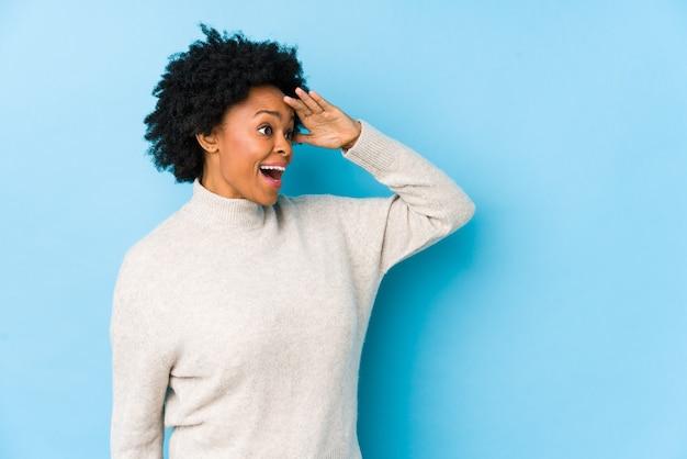 Afroamerikanerfrau mittleren alters gegen eine blaue wand lokalisiert, die weit weg schaut und hand auf stirn hält.