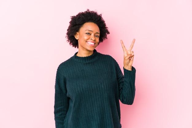 Afroamerikanerfrau mittleren alters gegen einen rosa hintergrund lokalisiert, der nummer zwei mit den fingern zeigt.