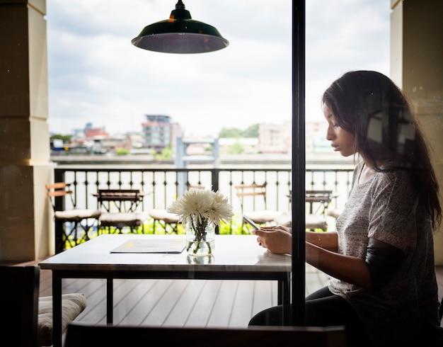 Afroamerikanerfrau sitzt alleine an einem café