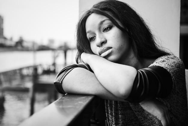 Afroamerikanerfrau sitzt und etwas erwägend