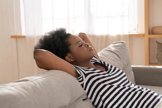 Afroamerikanerfrau tragen abgestreiftes t-shirt, das auf couch mit arm unter kopf zu hause schläft. sich ausruhen.