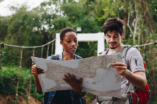 Afroamerikanerfrau und ein kaukasischer mann, der eine karte betrachtet