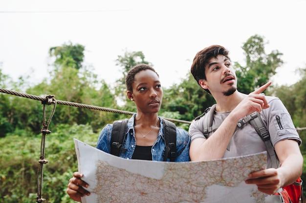 Afroamerikanerfrau und ein kaukasischer mann, der zusammen eine karte betrachtet, reisen und teamwork-konzept