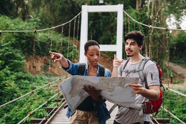 Afroamerikanerfrau und ein kaukasischer mann, die zusammen ein kartenreise- und -teamwork-konzept betrachten