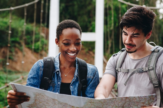Afroamerikanerfrau und ein kaukasischer mann, die zusammen eine karte betrachten, reisen