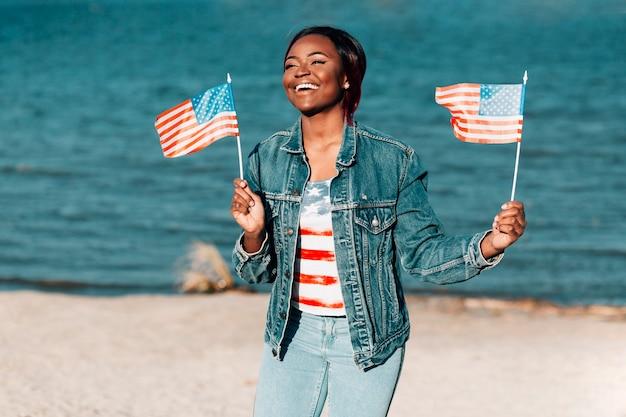 Afroamerikanerfrau, welche die amerikanischen flaggen stehen auf küste hält