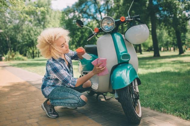 Afroamerikanerfrauen, die motorroller waschen. mädchen, das das blaue moped oder das motorrad säubert.