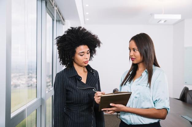 Afroamerikanerfrauen mit dokumenten nähern sich fenster im büro