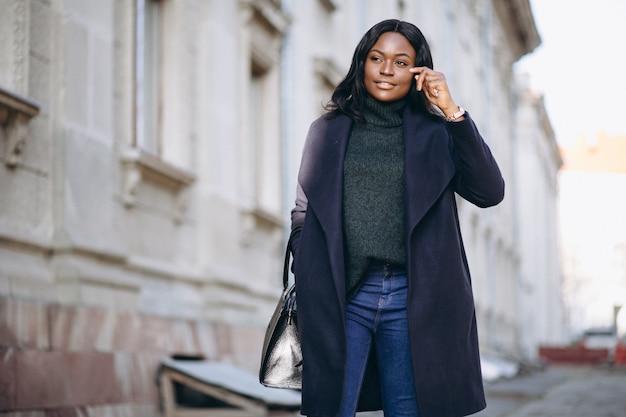 Afroamerikanerfrauenmodell im mantel in der straße