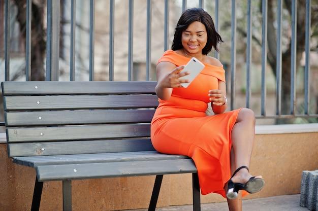 Afroamerikanerfrauenmodell xxl im orange kleid, das am handy schaut.