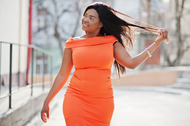 Afroamerikanerfrauenmodell xxl im orange kleid.