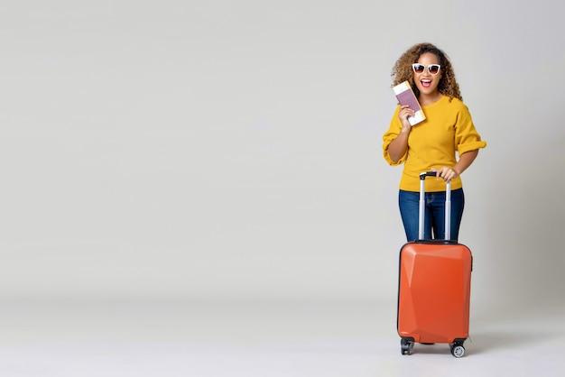 Afroamerikanerfrauentourist mit dem gepäck, das pass und bordkarte hält