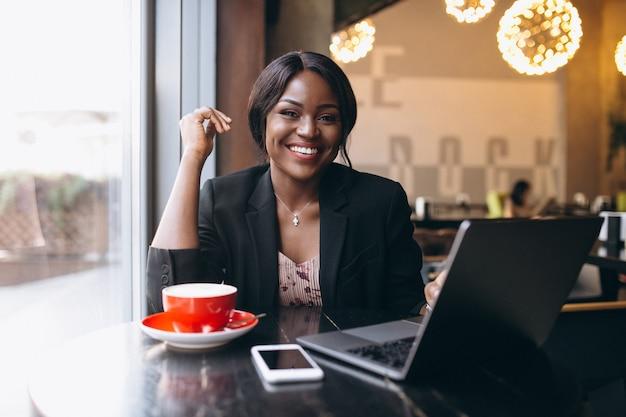 Afroamerikanergeschäftsfrau, die in einem café arbeitet
