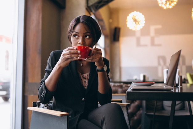 Afroamerikanergeschäftsfrau, die kaffee in einer bar trinkt