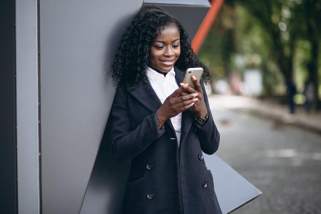 Afroamerikanergeschäftsfrau mit telefon außerhalb des cafés