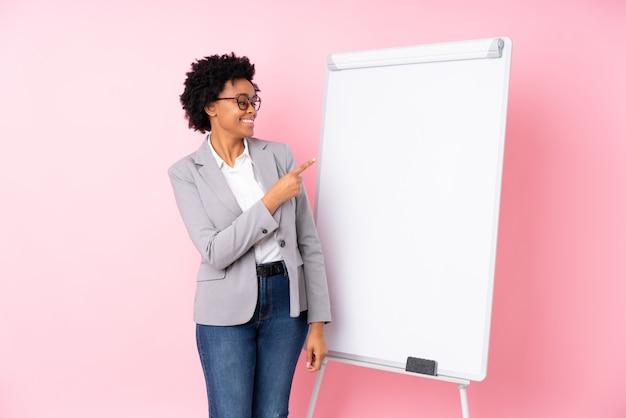 Afroamerikanergeschäftsfrau über rosa wand