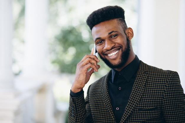 Afroamerikanergeschäftsmann, der am telefon spricht