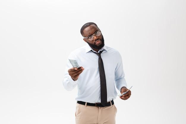 Afroamerikanergeschäftsmann, der bargeld und ernste schauende kamera hält. innen, lokalisiert auf grauem hintergrund.