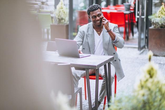 Afroamerikanergeschäftsmann, der laptop in einem café verwendet