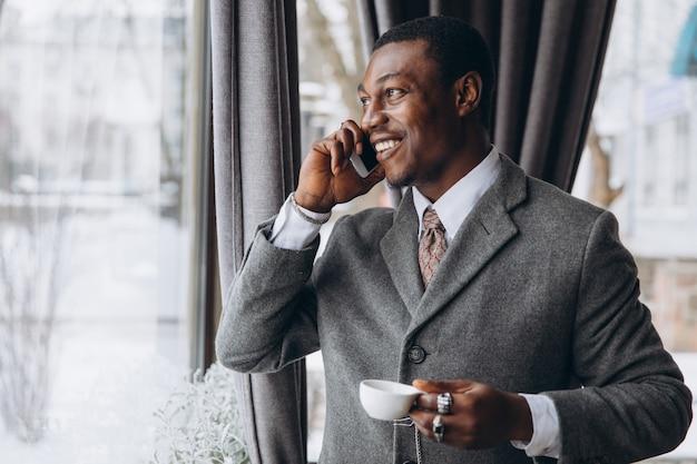 Afroamerikanergeschäftsmann hat gespräch auf einem smartphone und einem trinkenden tasse kaffee