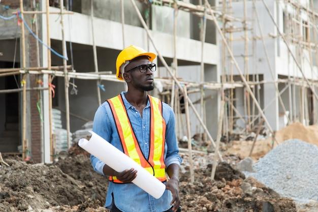 Afroamerikanergeschäftsmann im schutzschutzhelm, der blaupausenpläne auf der baustelle betrachtet.
