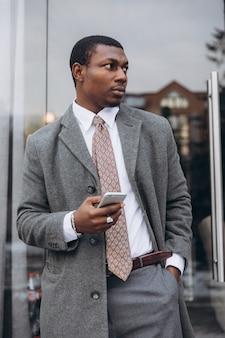 Afroamerikanergeschäftsmann in der klassischen grauen klage beim verlassen des bürogebäudes