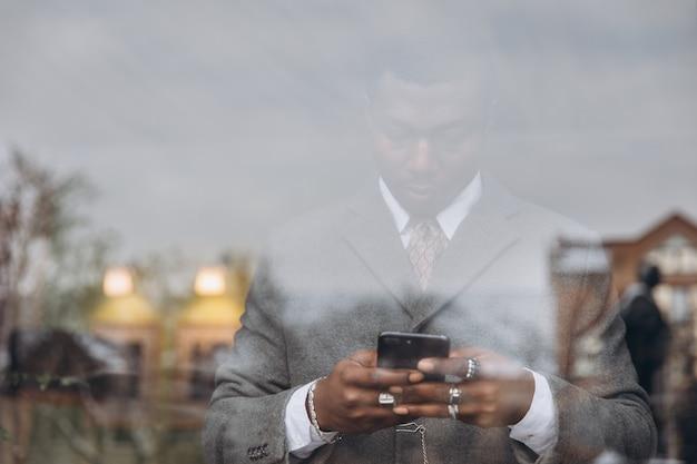Afroamerikanergeschäftsmann in der klassischen grauen klage, die einen smartphone hält.