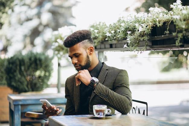 Afroamerikanergeschäftsmann in einem trinkenden kaffee des cafés