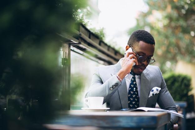 Afroamerikanergeschäftsmann-lesenachrichten und unterhaltung am telefon