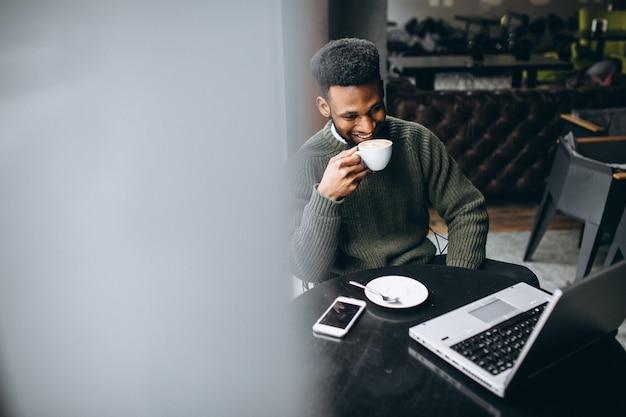 Afroamerikanergeschäftsmann mit laptop in einem café