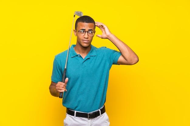 Afroamerikanergolfspieler-mann, der zweifel und mit verwirrtem gesichtsausdruck hat