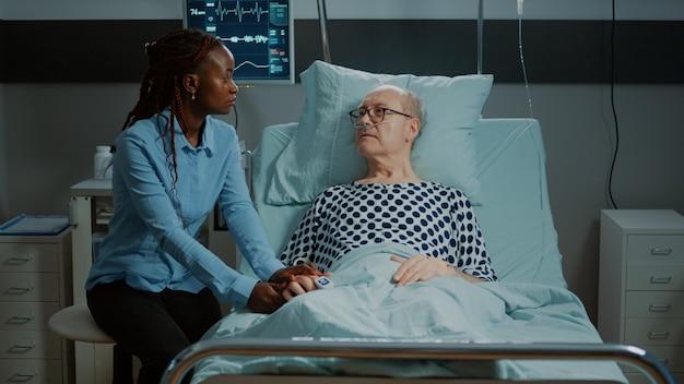Afroamerikanerin besucht kranke patienten im krankenbett in der medizinischen einrichtung alter mann mit oxi...
