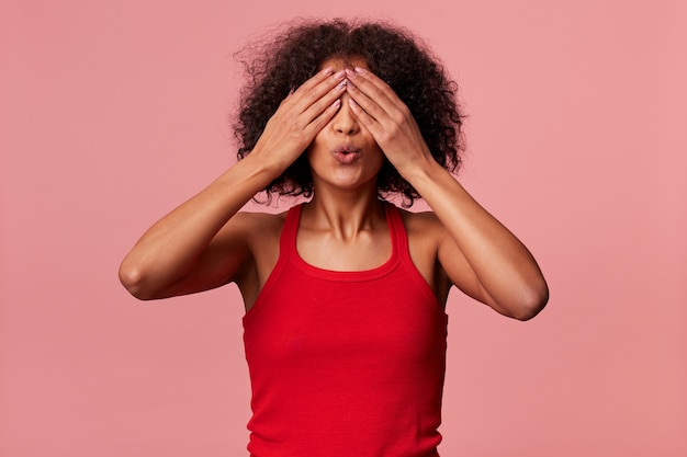 Afroamerikanerin der jungen schönheit mit dem gelockten dunklen haar, das rotes t-shirt tragend. bedeckt ihre augen mit den händen und macht sich bereit, isoliert zu küssen.