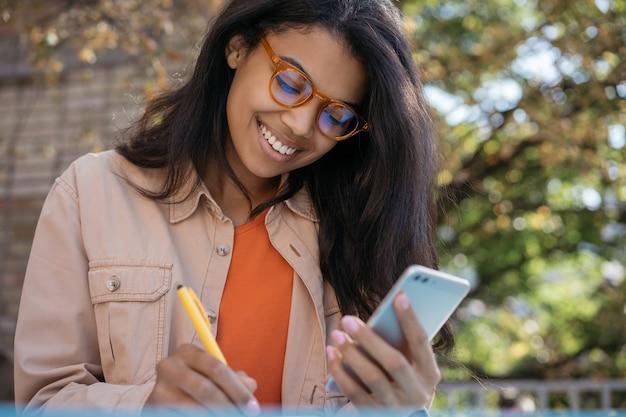 Afroamerikanerin, die arbeitet, handy benutzt, notizen macht, start plant, am arbeitsplatz sitzt